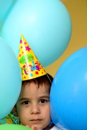 toddler boy with party hat and balloons